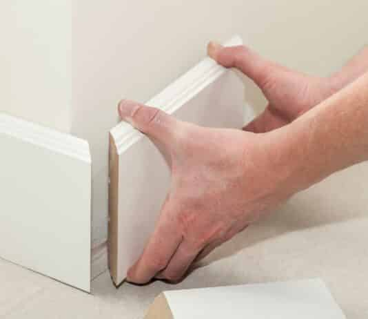 Man putting new skirting board in house