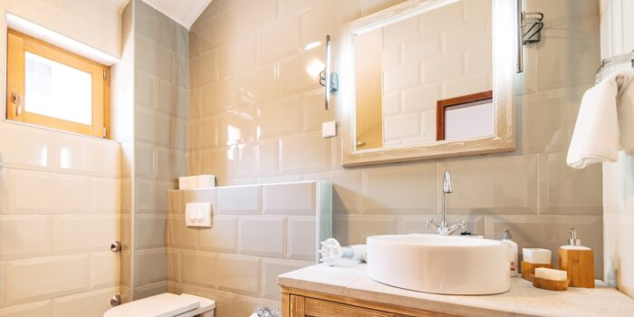 White washbasin with large mirror, towel holder and LED lamp in the bathroom next to the toilet and bidet. High quality photo