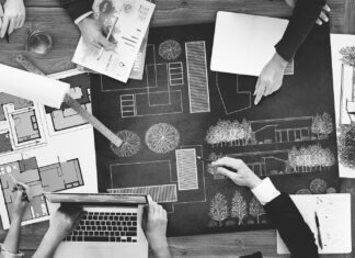 Serious concentrated man draws sketches, prepares blueprint, uses modern tablet, sits at home, isolated over grey background. Professional young male engineer with stubble being in modern office