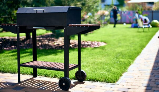 barbecue grill on wheels with wooden stands in the garden. tasty and wholesome food in the heat. future shish kebab. for holidays and events
