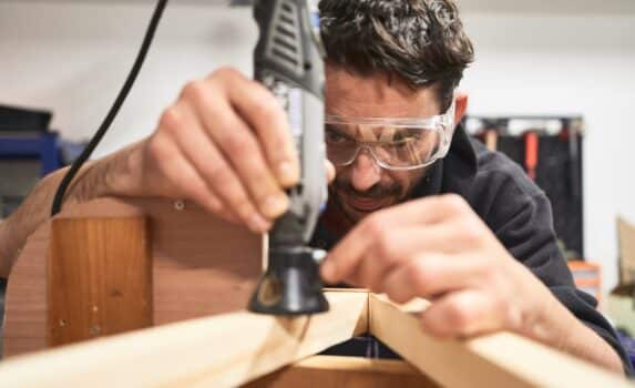portrait of young man with safety glasses working with a Dremel tool