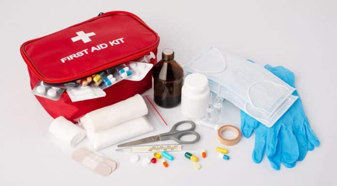 First aid kit on white table. Full set of emergency medicine, medication for giving first aid to a sick or injured person on white background