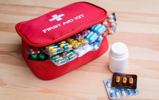 First aid kit with colorful capsules and pills on table. Remedy for diseases, healthcare, emergency.