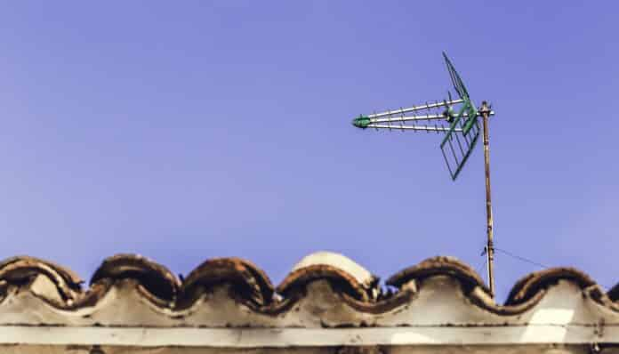 Television antenna on the old roof with blue sky background in Andalucia, Spain