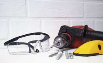 Professional tool for drilling. Electric drill with safety glasses on a brick wall background