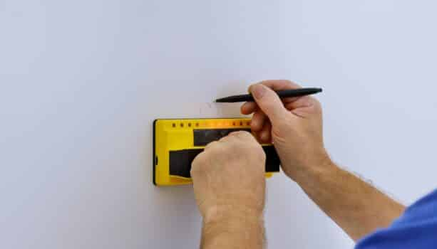 Man hand is scanning wall by uses multi-sense technology to find studs more accurately through difficult surfaces soft focus