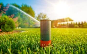 Lawn Sprinkler in Action. Garden Sprinkler Watering Grass. Automatic Sprinklers.