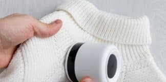 Man's hand holding a lint remover from a white acrylic or wool sweater. Electric device after cleaning and collected fluff/lint, light wooden background. Top view.