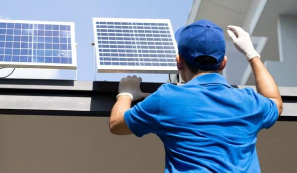 Asian workers technicians man installing solar photovoltaic panels for LED lamps on the roof of the house. Exterior solar cell system installation concept
