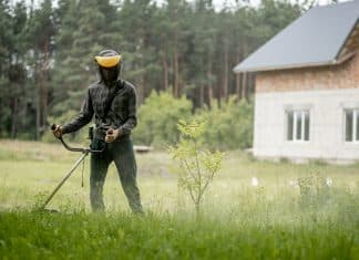 Man mowing the lawn in his garden. Gardener cutting the grass. Lifestyle