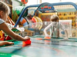 Two happy girls plays air hockey in children game center. Excited childs having fun on playground indoors. Kids playing on machine in amusement centre