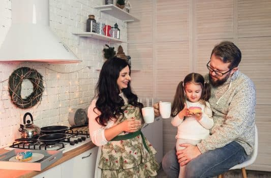 A woman treats her daughter and husband with tea and donuts