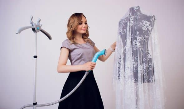 Women steaming dress in room seamstress professional