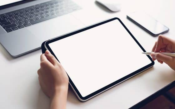 Woman using tablet screen blank and laptop on the table mock up to promote your products. Concept of future and trend internet for easy access to information.