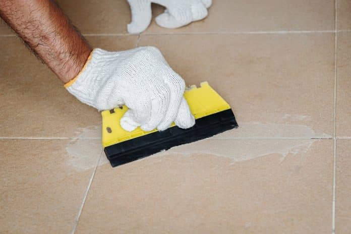 Construction worker in white gloves is working to grout the tiles in the bathroom.