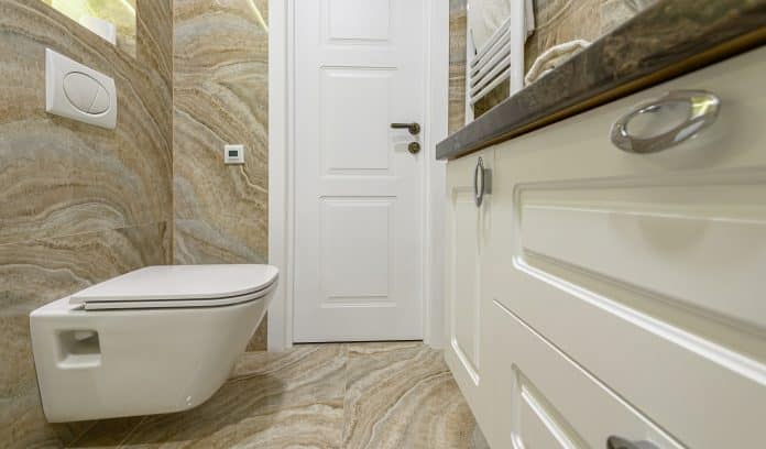 Spacous luxury bathroom with white water toilet, cabinet and beige marble tiles