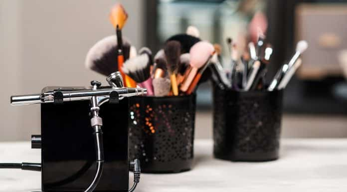 Beauty and fashion. Makeup tools and brushes on artist workplace. Makeup products set. Beauty salon treatment. Airbrush for makeup. Modern beauty women salon.