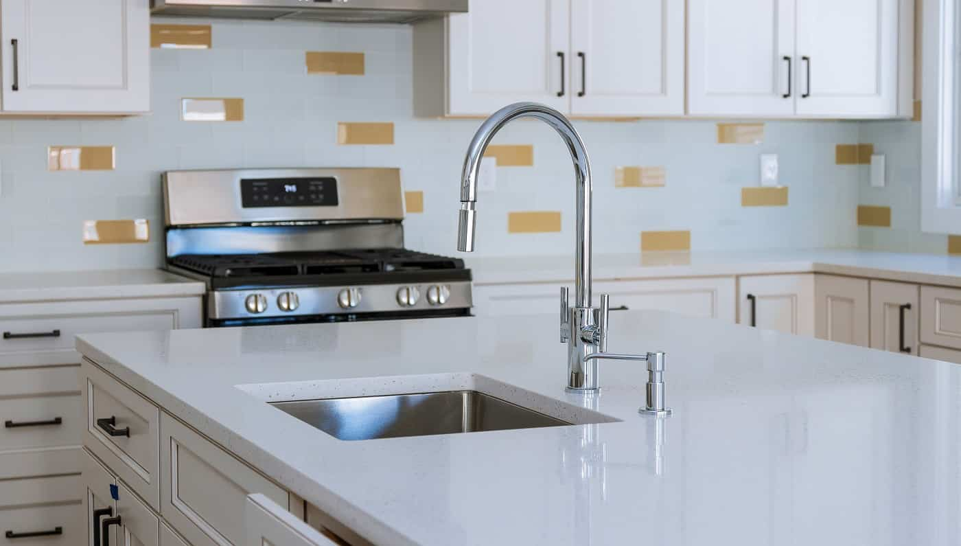 Modern domestic kitchen cabinets with new appliances and sink in kitchen
