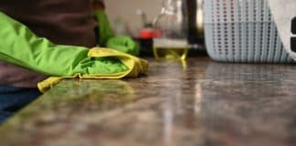 The girl washes the countertop in the kitchen. High quality photo