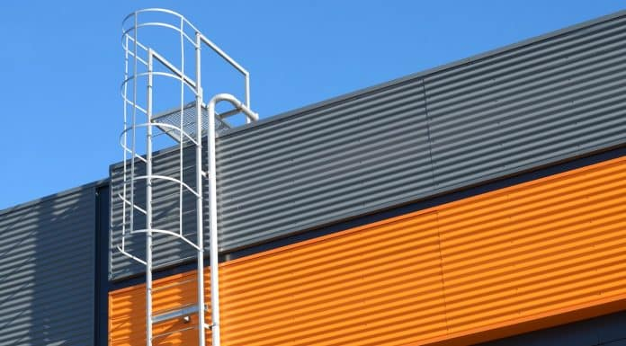 Metal fire escape stairs or ladder to roof on a wall of building