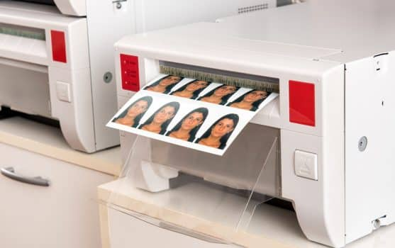Printing passport photos of a woman on a printer with a sheet of eight photographs exiting the machine in a close up view