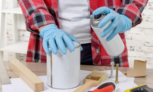 A young man with aerosol paint and blue gloves