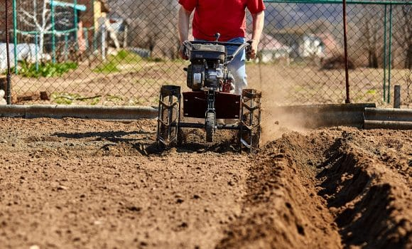 Gardener man cultivate ground soil with tiller tractor or rototiller, cutivator, miiling machine, prepare for planting crop in spring. Modern farming, technology agriculture.
