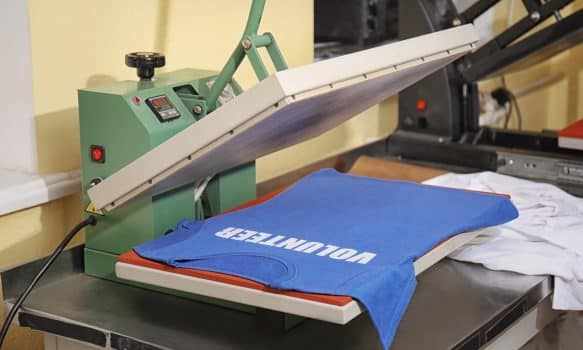 Modern printing machine with t-shirt at workplace