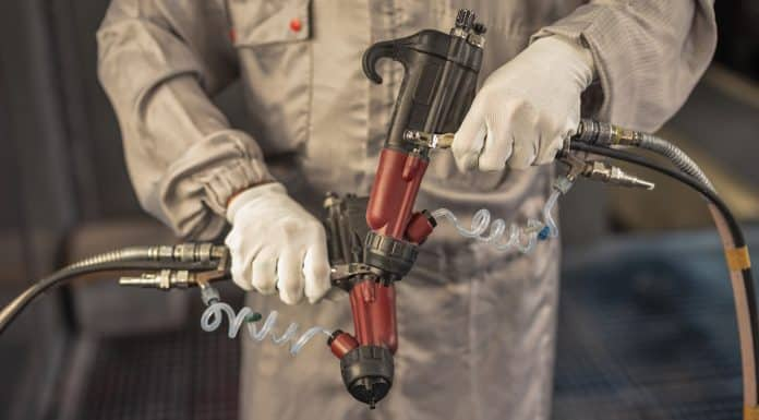 Paint shop worker with industrial sprayers in his hands, close-up
