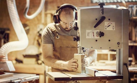 Detail of a carpenter at work cutting a plank with a band saw in his workshop, caucasian with a beard, apron and protective glasses.