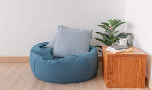 Blue bean bag in a clear living room with wooden floor and clear white wall.