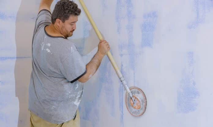 Contractor using sand trowel sanding the drywall on the wall