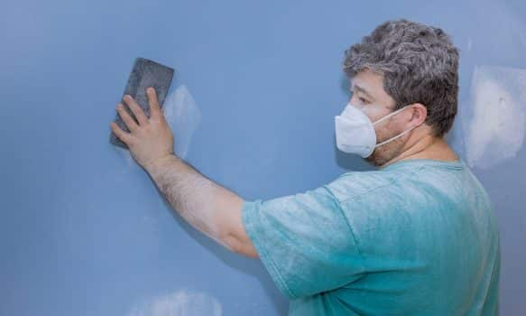 Worker sanding the drywall mud using sand trowel during renovation the house on room