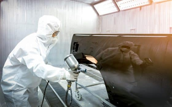 Automobile repairman painter in protective workwear and respirator painting car body in paint chamber