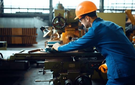 Worker in uniform and helmet works on lathe, plant. Industrial production, metalwork engineering, power machines manufacturing