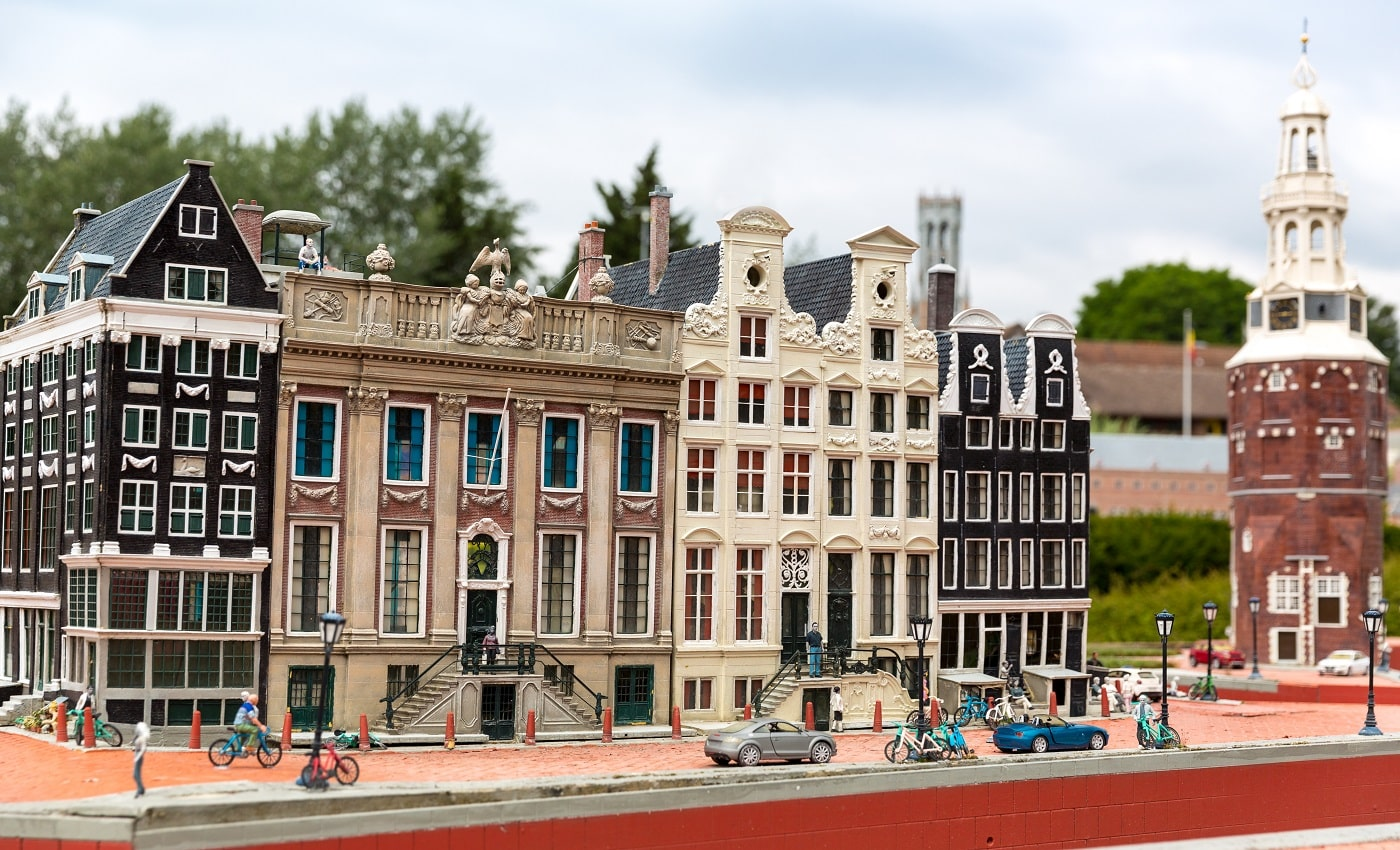 People on the street, ancient building, cyclists, miniature scene outdoor, europe. Mini figures with high detaling of objects, realistically diorama