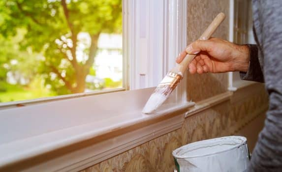 Male hands repairs painting window trim at home closeup