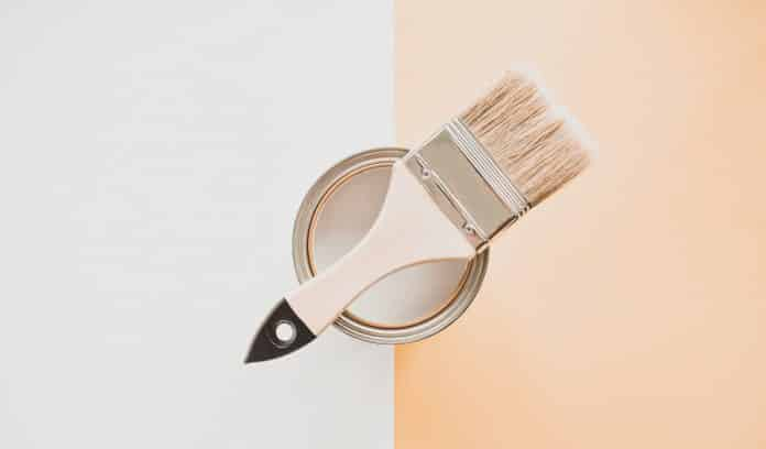 One open can of white paint with a brush, on a bright background. The view from the top. The concept of renovation.