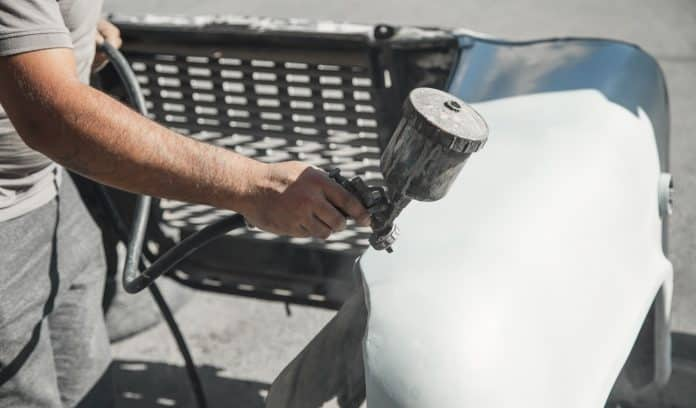 Spray gun in the hand of a painter. Painting car details