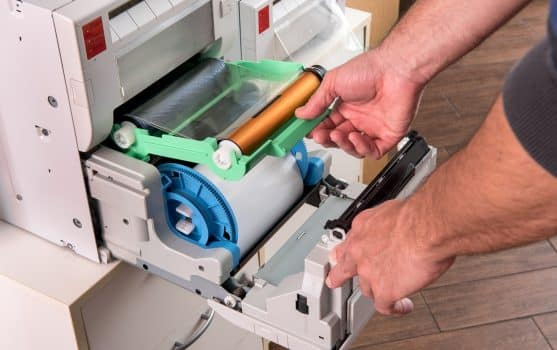 Man changing the ribbon on a photographic printer