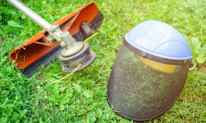 String trimmer and protective face mask on grass