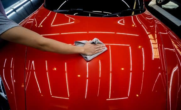 Car service worker applying nano coating on a car detail. Tools for polishing