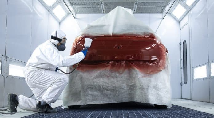 Professional painter in protective clothing applying varnish layer and finishing painting of the car.