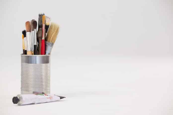 Varieties of paint brushes in metallic jar and tube color against white background