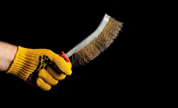 Close up hand of craftsman in a glove holds brush for removing rust