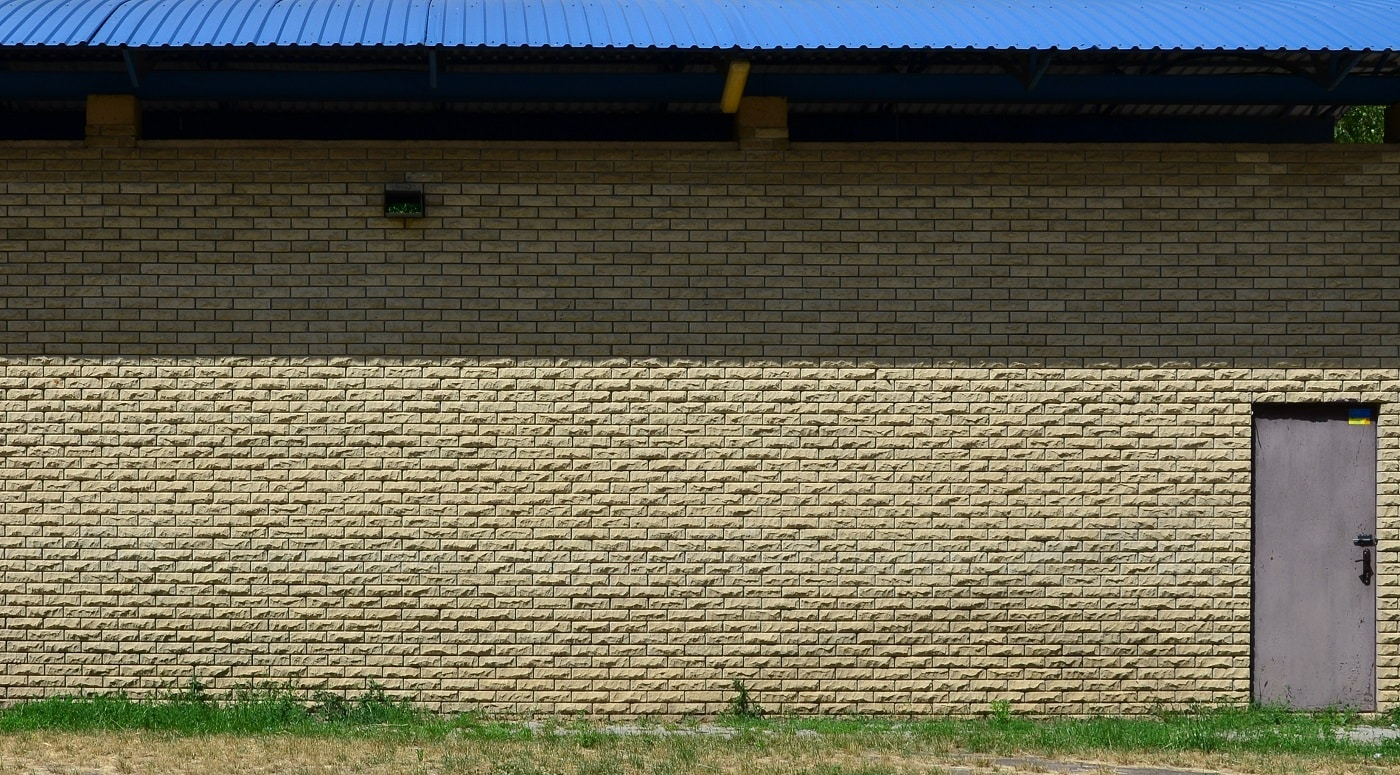Texture of brick wall from relief stones under bright sunlight with two metal doors