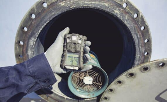 Worker hand holding gas detector inspection safety gas testing at front manhole stainless tank to work inside confined