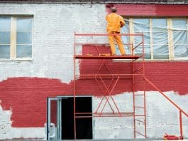 Man painting a brick wall in red