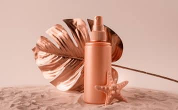 Sunscreen cream or lotion bottle with tropical monstera leaf colored in rose gold. Healthcare while vacationing concept.