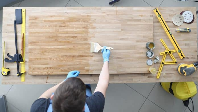 Master apply wood preservative with brush at workplace. Construction tool and equipment are on desktop. Furniture manufacturing and apartment renovation concept.